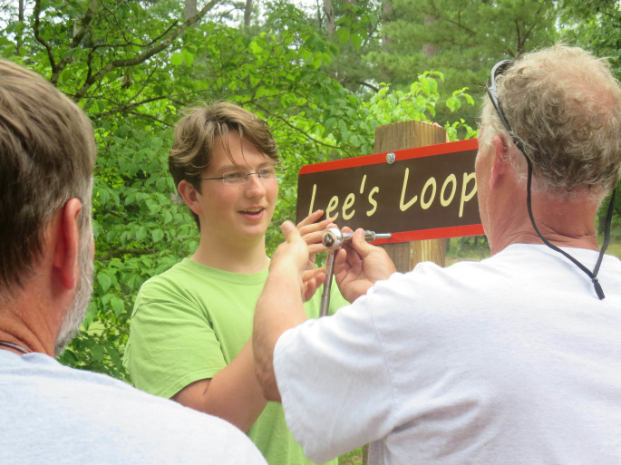 William Douglas puts the final touches on trail signage at Jackson Hill.